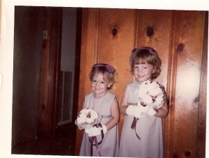 Purple flower girls in front of paneling.